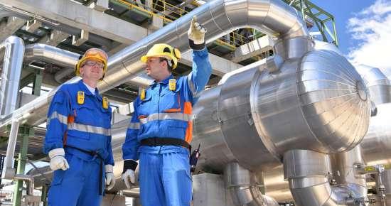 Teamwork: zusammenarbeit von industriellen Arbeitern in einer Erdölraffinerie // Teamwork: collaboration of industrial workers in a petroleum refinery